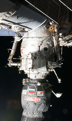 Pirs (ISS module) - Pirs with a docked Progress spacecraft. Note the two Strela robotic arms and the airlock door.