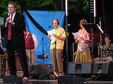 full length portrait of Garrison Keillor with a microphone and three performers behind him and someone seated on the stage