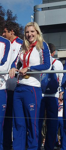 Young woman in blue tracksuit pants, white top with blue long sleeves, wearing a gold medal around her neck with red ribbon. She has long blonde hair, large nose and is leaning on a rail, and is surrounded by similarly dressed people.