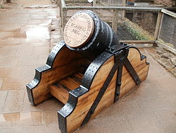 "A squat black mortar, the end gapped with a wooden plug on which is carved ""Roaring Meg""; the mortar has wooden supports with black metal brackets."