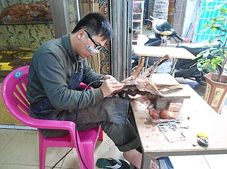 Root carving - A craftsman works on a piece in Haikou City, Hainan Province. His shop is located in an area beside East Lake, part of Haikou People's Park. The area contains dozens of small shops dedicated to producing root carvings.