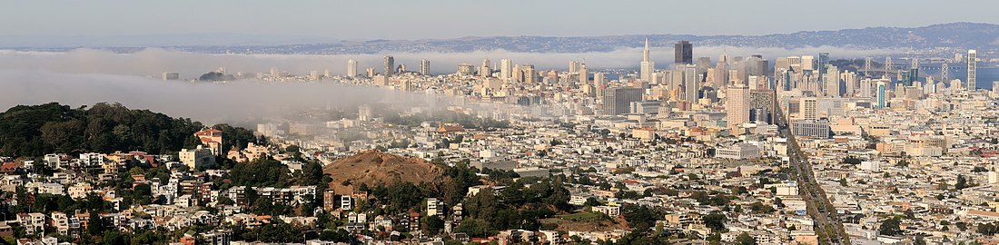 Panoramische foto van San Francisco met opkomende mist. De groene heuvel links in beeld is het Buena Vista Park. De kale heuvel rechts daarvan is het Corona Heights Park. Market Street is de brede verticale as rechts op de foto.