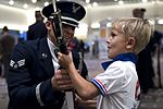 Senior Airman Angelo Hightowe lets a young boy hold a drill rifle (31908304200).jpg
