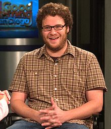 A Caucasian male wearing dark glasses, brown, curly hair, and a brown beard. He is sitting on a chair, laughing, wearing a yellow buttoned shirt.