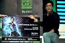 Shah Rukh Khan standing beside  a large box with his character's picture on it