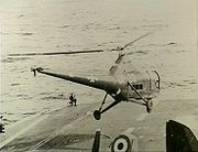 """The forward section of an aircraft carrier's flight deck. A helicopter with United States markings and the letters """"UP-28"""" painted on the side is hovering just above."""