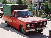zaparkovaný červený pick-up shranatou karoserií