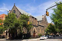 A view from across the street of St. Paul's Church in Carroll Gardens, Brooklyn—a brick building with a small stained glass windows and a grey roof