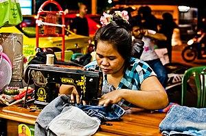 Sewing - A woman sewing as a street vendor in Bangkok, Thailand.