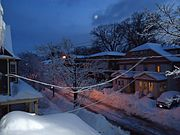 Summit New Jersey street after snowfall in early morning with houses and porches and car and moon