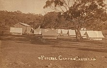 Single wooden cabin and many white tents in open dusty field with single tree in foreground