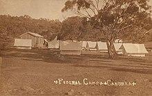 Cabana de madeira única e muitas tendas brancas em campo aberto empoeirado com uma única árvore em primeiro plano