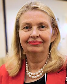 Head-only portrait of a blond woman in her sixties wearing bright red lipstick