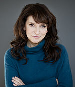 Photo of Susanne Bier standing in front of a grey wall in 2013.