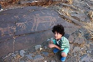 Rock art in Iran - Curious boy sitting near petroglyphs