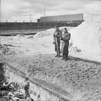 Leslie Hardman - Leslie Hardman, and Roman Catholic Padre Father M.C. Morrison, conduct a service over Mass Grave number 2 at Belsen before it is filled in. 25 April 1945