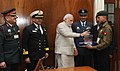 The Prime Minister, Shri Narendra Modi donating after pinning a flag by the Officers of the Kendriya Sainik Board, during the Armed Forces Flag Day, in New Delhi on December 05, 2014.jpg