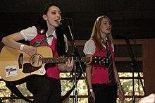 Deux jeunes filles en train de chanter (une brune à gauche jouant de la guitare et une blonde à droite). Elles portent des gilets rose foncé sans manches sur des chemisiers blancs, avec des cravates vertes visibles