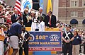Timothy Cherigat, winner of the 108th Boston Marathon, at Marathon Award Ceremony as Mayor Thomas M. Menino and others look on (22394790619).jpg