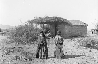 Mohave people - Two Mojave girls standing in front of a small dwelling with a thatched roof, 1900