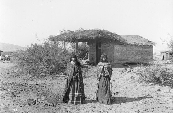 Two Mojave girls standing in front of a small dwelling with a thatched roof, 1900 Two Mojave Indians girls standing in front of a small dwelling with a thatched roof, 1900 (CHS-1241).jpg