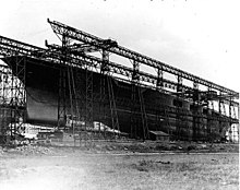 Large ship with no superstructure with scaffold-like steel surrounding her.