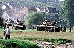 US Army tanks maneuvering for a river crossing during REFORGER '82 with German village in background DF-ST-99-04887.jpg
