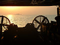 US Navy 031015-N-0000M-001 The sunrises behind a Landing Craft Air Cushion (LCAC) during well deck operations aboard USS Peleliu (LHA 5), lead ship for Expeditionary Strike Group One (ESG-1).jpg