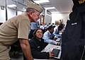 US Navy 041019-N-2383B-186 Chief of Naval Operations (CNO), Adm. Vern Clark, looks over the shoulder of Aviation Electronics Technician 1st Class Megan Reiger of Strawberry, Ariz., in a temporary classroom set-up at Naval Aviat.jpg