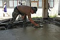 US Navy 060530-N-3931M-050 A Seabee assigned to Naval Mobile Construction Battalion Four Zero (NMCB-40) levels fresh poured cement for a walkway to a medical building at the Zamboanga Medical Center.jpg