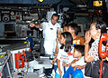 US Navy 060816-N-5747D-004 Guided-missile destroyer USS Hopper (DDG 70) Weapons Officer, Lt. Ernesto Almonte, explains some of the day-to-day operations that take place in the ship's Combat Information Center to local school ch.jpg