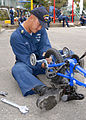 US Navy 071101-N-4649C-066 Machinery Repairman 1st Class Solomon Samonte, assigned to submarine tender USS Frank Cable (AS 40), repairs a bike at the Shunko Gakuen orphanage.jpg