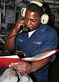 US Navy 081202-N-6764G-065 Engineman 3rd Class Paris Pharisien gives a status reports during a roving watch.jpg