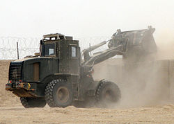 US Navy 090330-N-8547M-020 A Seabee assigned to Naval Mobile Construction Battalion (NMCB) 5 uses an up-armored front-end loader to fill a HESCO barrier.jpg