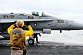 US Navy 090530-N-3946H-082 A Chief Aviation Boatswain's Mate guides an F-A-18C Hornet.jpg