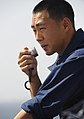 US Navy 090916-N-5345W-107 nsign Kenneth Lee communicates with the amphibious dock landing ship USS Fort McHenry pilot house while operating as the ship's conning officer during a connected replenishment at sea.jpg