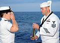 US Navy 100609-N-7908T-291 Lt. Sunny Mitchell salutes Machinist's Mate 1st Class Wesley D. Hatley during a burial at sea for his father.jpg