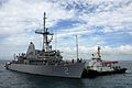 US Navy 110815-N-SP676-106 A tug boat pulls the mine countermeasures ship USS Defender (MCM 2) into White Beach Naval Facility, Okinawa, during a d.jpg