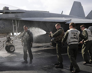US Navy 111222-N-RG587-208 Cmdr. John Boone, commanding officer of Strike Fighter Squadron (VFA) 81, is hosed down after making his final landing a.jpg