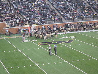 Time-out (sport) - Time out during a 2012 game between the Wake Forest Demon Deacons and Boston College Eagles.  Two officials, the referee and the umpire, stand over the ball while the teams confer during the time out.