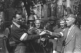 5th SS Panzer Division Wiking - Warsaw Uprising insurgents inspect war trophies including an armband with the Wiking name