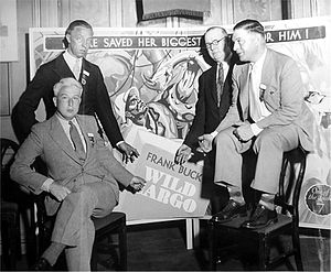 Wild Cargo (film) - Director Armand Denis (seated right) with RKO exhibitors and poster for Wild Cargo (ca. 1934)