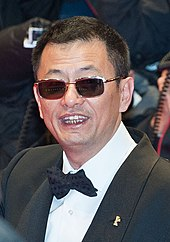 Wong Kar-wai at a film festival. He is wearing sunglasses and sports a buzzcut hairstyle in tuxedo and a bowtie