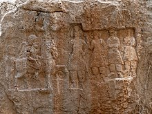 Faded relief carved into the side of a rock. The scene portrays a man on horseback as well as several other characters.