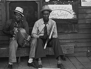 "Zydeco - Early Creole musicians playing an accordion and a washboard in front of a store, near Opelousas, Louisiana (1938). Zydeco music originated from Creole music — today's rubboard or frottoir (""rubbing the washboard"") is a stylized version of the early washboard."