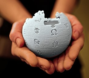 A 3D-printed Wikipedia globe being held in someone's hands