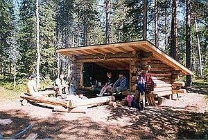 Ihmisiä nauttimassa auringosta puulaavulla.