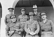 Six senior Australian officers pose for a formal picture. Two are wearing slouch hats, the remainder are wearing peaked caps. All have multiple ribbons.