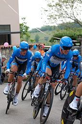A group of cyclists wearing the same blue and black uniform while riding bikes.