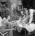 A US serviceman having tea with ex-Mayor of Winchester, Mr Edmonds, and his wife and daughter in the garden of their home during 1944. D21572.jpg